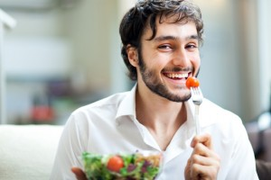 young-smiling-man-eating-a-salad